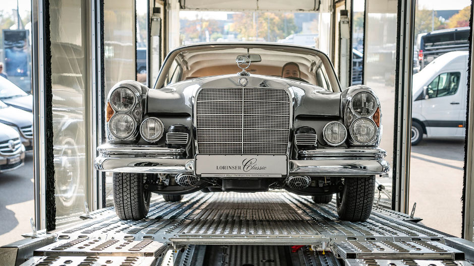 Noble. A 1966 Mercedes-Benz 300 SE/C ascends the loading ramp of the closed car transporter.