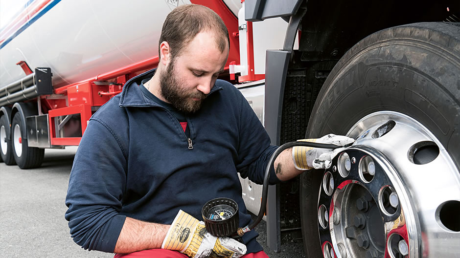 Speedy aid. After the message in the display of his Actros, driver Jan Hettling checks the tyre pressure on the front axle. In the background, Mercedes-Benz Uptime fleet manager Sascha Schmieder supplies all the details about the loss of pressure via the online customer portal.